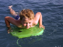 el muchacho está practicando surf en el océano Imagen de archivo libre de regalías