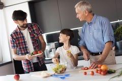 El muchacho está preparando una ensalada para la cena el día de la acción de gracias con su padre y abuelo Fotos de archivo libres de regalías