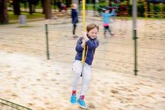 El muchacho está resbalando abajo de una cuerda Imagen de archivo libre de regalías
