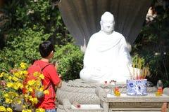 El muchacho está rogando la estatua de Buda en pagoda Imágenes de archivo libres de regalías