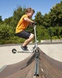 El muchacho está saltando con una vespa sobre una espina dorsal en el parc del patín y Foto de archivo