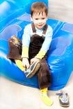 El muchacho está sentando, calza los zapatos Fotografía de archivo libre de regalías