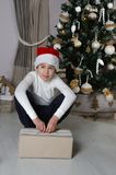 El muchacho está soñando sobre el regalo mientras que abre la caja envuelta Imagenes de archivo
