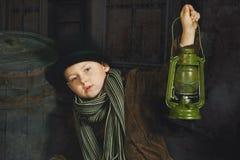 El muchacho está sosteniendo una lámpara de keroseno vieja en sus manos Retrato retro estilizado Imagen de archivo