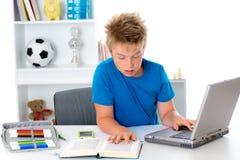 El muchacho está trabajando con el libro y el ordenador Imagen de archivo