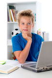 El muchacho está trabajando con el libro y el ordenador Foto de archivo
