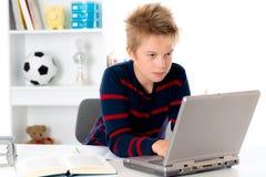 El muchacho está trabajando con el libro y el ordenador Fotografía de archivo libre de regalías