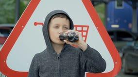 El muchacho est? bebiendo de una botella pl?stica, c?mara lenta almacen de metraje de vídeo