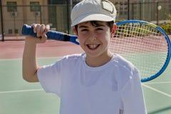 El muchacho está jugando a tenis Fotografía de archivo libre de regalías