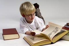 El muchacho está leyendo los libros gruesos Imágenes de archivo libres de regalías