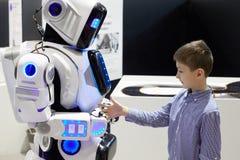 El muchacho estira hacia fuera su mano al robot como muestra de amigos Imagen de archivo libre de regalías