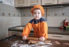 El muchacho europeo lindo en un traje del cocinero hace las galletas del jengibre fotografía de archivo
