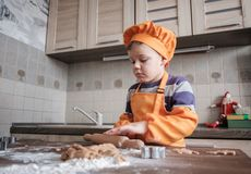 El muchacho europeo lindo en un traje del cocinero hace las galletas del jengibre fotografía de archivo libre de regalías