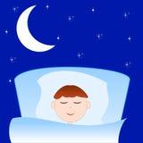El muchacho exhausto duerme en una cama Fotos de archivo libres de regalías
