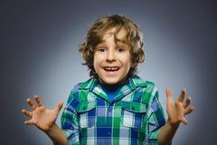El muchacho feliz acertado del retrato del primer aisló el fondo gris Imagen de archivo