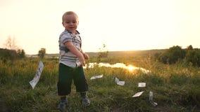 El muchacho feliz aumenta el dinero de la hierba y lanza los billetes de dólar en la cámara lenta almacen de metraje de vídeo