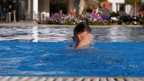 El muchacho feliz con las aletas nada en una piscina con agua azul C?mara lenta metrajes