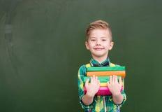 El muchacho feliz con los libros acerca a la pizarra verde vacía Imágenes de archivo libres de regalías