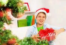El muchacho feliz con los presentes acerca al árbol de navidad Imágenes de archivo libres de regalías