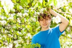 El muchacho feliz del adolescente lleva a cabo la rama con las flores blancas Imagenes de archivo