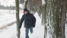 El muchacho feliz del niño corre entre los árboles y entonces los soportes y la sonrisa metrajes