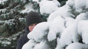 El muchacho feliz del niño juega con las ramas de árbol nevosas de abeto, bosque del invierno, paisaje hermoso metrajes