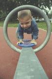 El muchacho feliz del niño que jugaba seesawing en patio en el parque filtró efectos Imagen de archivo libre de regalías
