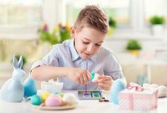 El muchacho feliz del niño que se divierte durante la pintura eggs para Pascua en primavera fotos de archivo