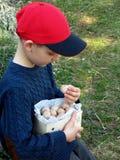 El muchacho feliz en casquillo rojo está comiendo el buñuelo Anillos de espuma de la avena con canela, azúcar en polvo y café Buñ Imágenes de archivo libres de regalías