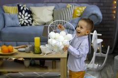 El muchacho feliz en la Navidad está jugando con la cesta con nieve falsa fotos de archivo