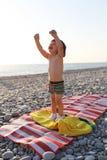 El muchacho feliz en los guijarros vara en la puesta del sol Foto de archivo
