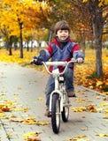 El muchacho feliz en parque del otoño monta su bici foto de archivo libre de regalías
