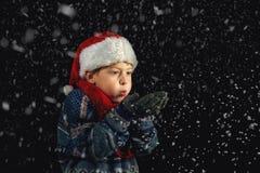 El muchacho feliz en el sombrero de Papá Noel juega con los copos de nieve en un fondo oscuro Imagen de archivo libre de regalías