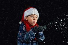 El muchacho feliz en el sombrero de Papá Noel juega con los copos de nieve en un fondo oscuro Fotografía de archivo libre de regalías