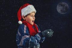 El muchacho feliz en el sombrero de Papá Noel juega con los copos de nieve en un fondo oscuro Foto de archivo