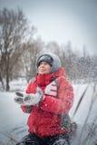El muchacho feliz en una nieve acumulada por la ventisca se sienta y ríe Foto de archivo libre de regalías
