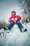 El muchacho feliz en una nieve acumulada por la ventisca se sienta y ríe Imagen de archivo