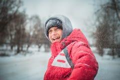 El muchacho feliz en una nieve acumulada por la ventisca se sienta y ríe Foto de archivo
