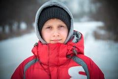 El muchacho feliz en una nieve acumulada por la ventisca se sienta y ríe Fotos de archivo libres de regalías