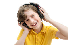 El muchacho feliz escucha música con los auriculares Imagenes de archivo