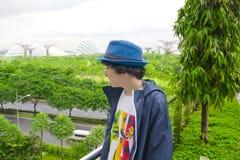 El muchacho feliz está en el jardín al lado de la bahía, Singapur Foto de archivo