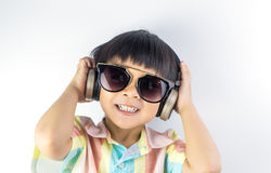 El muchacho feliz está escuchando la música en el auricular aislado Foto de archivo