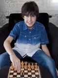 El muchacho feliz está jugando a ajedrez Foto de archivo libre de regalías