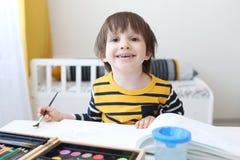 El muchacho feliz está pintando con la acuarela Foto de archivo libre de regalías