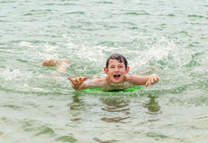 El muchacho feliz goza el practicar surf en las ondas imagenes de archivo
