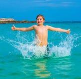 El muchacho feliz joven con el pelo marrón goza el nadar Fotos de archivo