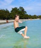 El muchacho feliz joven con el pelo marrón goza el saltar en el hermoso Fotos de archivo libres de regalías