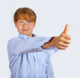 El muchacho feliz joven lindo en estudio muestra los pulgares para arriba Imagenes de archivo