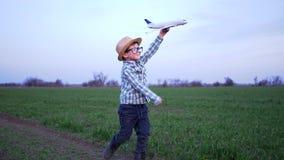 El muchacho feliz juega al aire libre con el aeroplano del juguete en campo verde en el fin de semana en la cámara lenta almacen de video