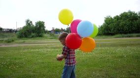 El muchacho feliz juega con el globo en el parque El caminar y actividades al aire libre metrajes